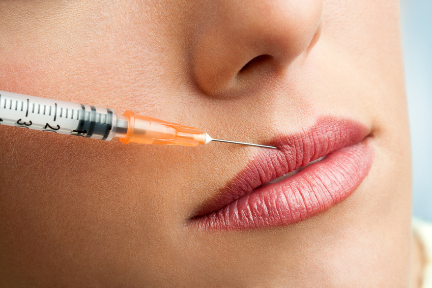 Macro botox syringe on female lips.